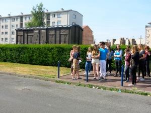 Groupe d'élèves pendant la visite guidée sur l'esplanade Charles de Gaulle, devant la Cité de la Muette de Drancy.