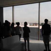 Mes élèves, dans la salle d'exposition permanente, observent les bâtiments de l'ancien camp que permet la façade transparente